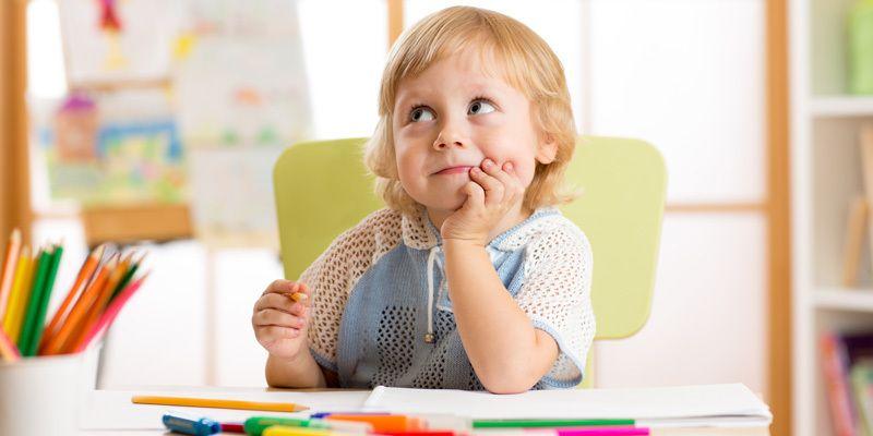 Criança em ambiente escolar refletindo sobre algo.