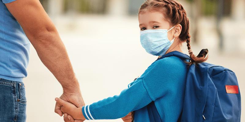 Menina com máscara contra a Covid-19 caminhando segurando a mão de seu pai.