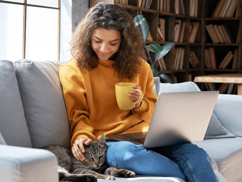 Mulher relaxada com notebook no colo, uma xícara na mãe e acariciando um gato.