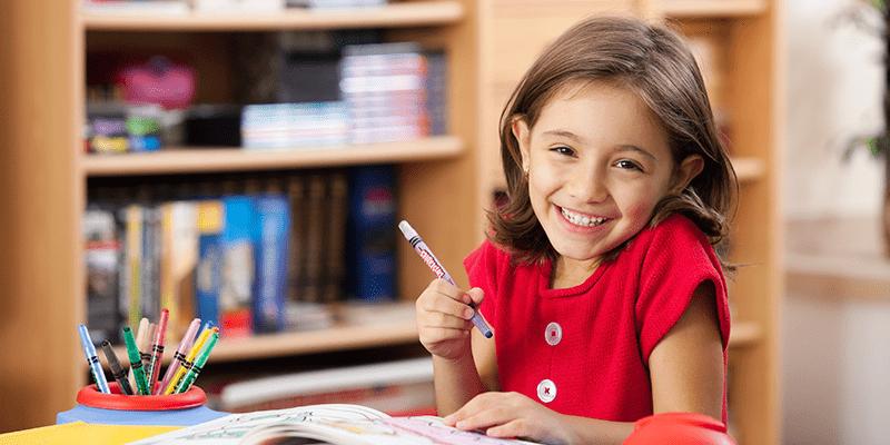 Menino em um ambiente escolar, segurando um lápis e sorrindo para a frente.