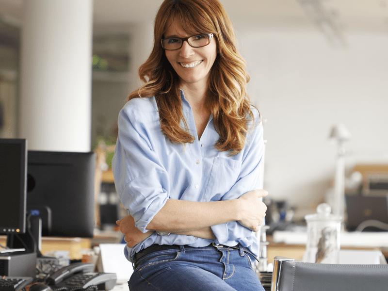Mulher de óculos com os braços cruzados e sorrindo.