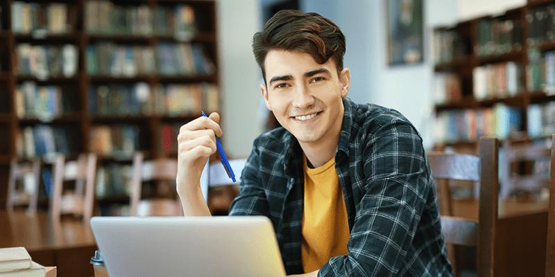homem jovem segurando um lápis na mão e sentado na frente de um notebook